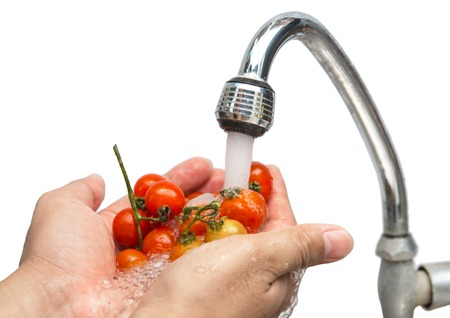 Hands cleaning tomatoes under the water Tap. Healthy concept.focus on tap,on isolated white Background. photo