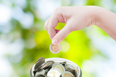 gratuity: woman hand putting a coin on green nature background,saving ,Donation Investment Fund Financial Support Charity  Dividend Market Growth