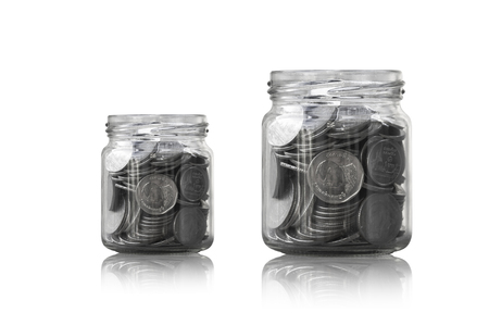 frugality: coins in a glass jar against ,savings coins - Investment And Interest Concept saving money concept, growing money on piggy bank. isolated on white background