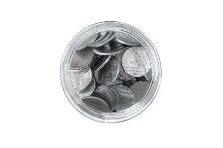 frugality: coins in a glass jar against top view ,savings coins - Investment And Interest Concept saving money concept, growing money on piggy bank. isolated on white background