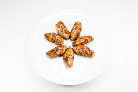 drumsticks: Grilled chicken wings in dish white on white background