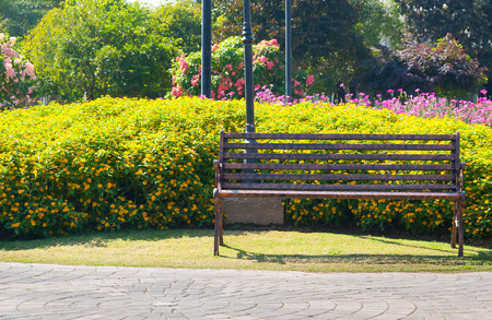 Lonely metal Decorative bench in the flower garden Stock Photo