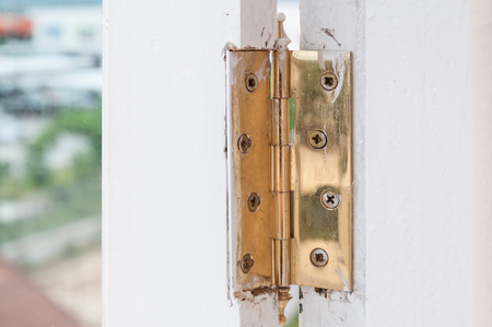Golden hinges on the protection of armored doors,Metal hasp on wood window Stock Photo