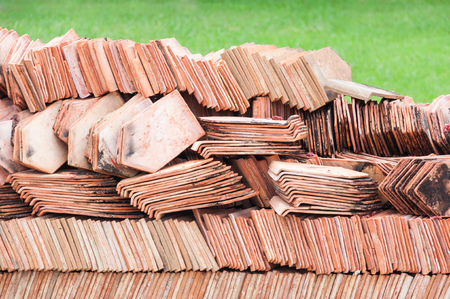 Heap red corrugated tile element of roof retro for construction,ready to use in construction site in temple Thailand Stock Photo