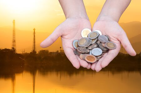 Coins in hands on Industry  silhouette Landscape background,Donation Investment Fund Financial Support Charity  Wealthy Giving Planned Accounting Collection Debt Banking ROI concept Stock Photo