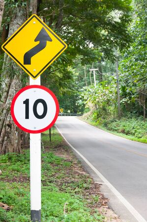 trip hazard sign: Selective speed limit traffic sign 10 and winding road caution symbol for safety drive in country road in mountain view forest,low key