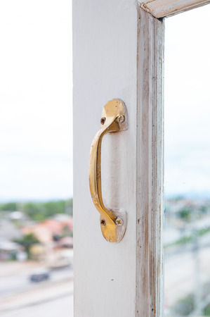 Golden Stainless steel vintage style handle on painted wooden white window, Furniture handles
