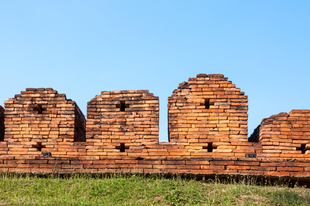 A portion of the ancient fortified city wall built of brick with cross bow cutouts and crenelations, Chiang Mai, Thailand ,Image of Fortress Stock Photo