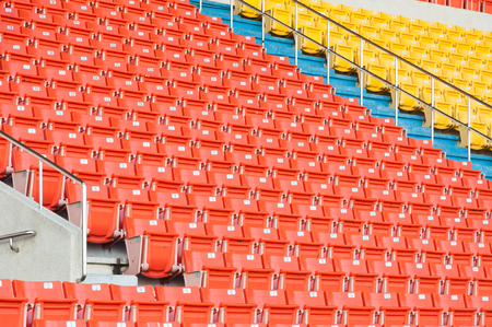 Empty orange and yellow seats at stadium,Rows of seat on a soccer stadium