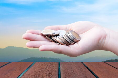 Coins in hands on Landscape background,Donation Investment Fund Financial Support Charity  Dividend Market Growth Home