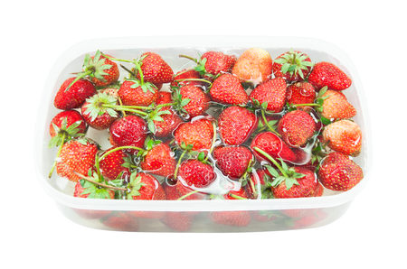 red freshly Strawberry inside cold water, sweet spring strawberries closeup, on white background Stock Photo