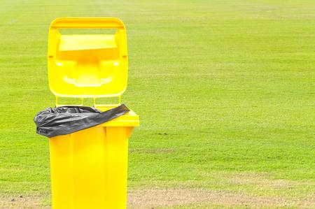 segregate: yellow Garbage bins on green grass background Stock Photo