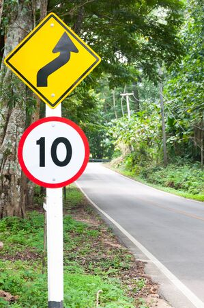 Selective speed limit traffic sign 10 and winding road caution symbol for safety drive in country road in mountain view forest,low key
