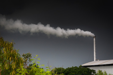 causing: Huge factory chimney polluting the air,Tall chimney emitting  water vapor and smoke Pollution,Industry Causing Pollution Stock Photo