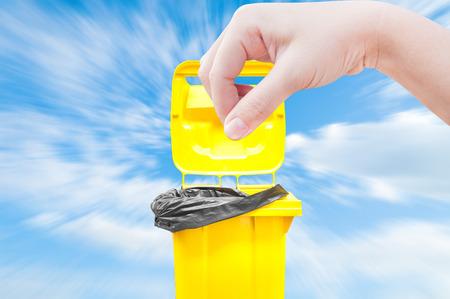hand women Pick catch , yellow Garbage bins on blue sky