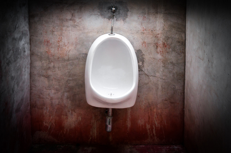 urinal on old concrete red wall,scary toilet Stock Photo