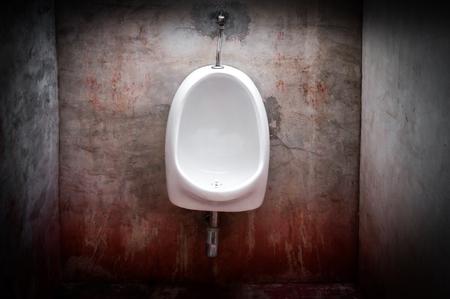urinoir sur vieux mur de béton rouge, toilettes effrayantes