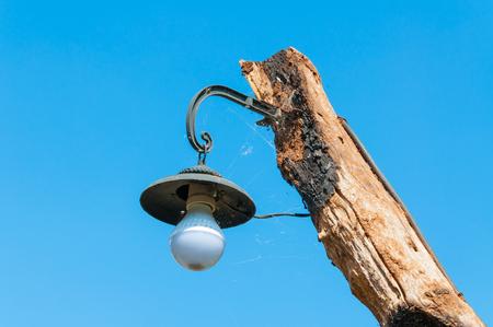 old lamp on post wood on bluesky