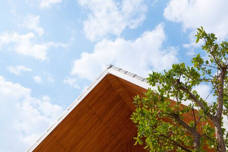 Wooden gabled roof with blue sky,triangles roof house sky background Stock Photo