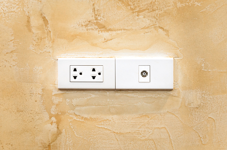 power cables: Power socket at the corner of a wall,electric ethernet and antenna socket on concrete wall