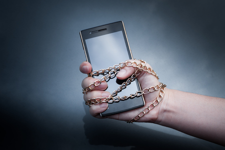 Lock chain smartphone hand woman holding ,Information security,Personal data security and protection concept - metal chain link hand with locked padlock on smartphone on dark background
