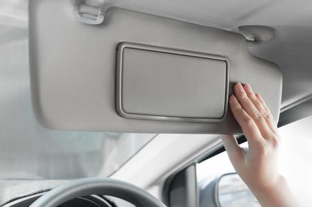 woman hand holding sun visor interior inside car