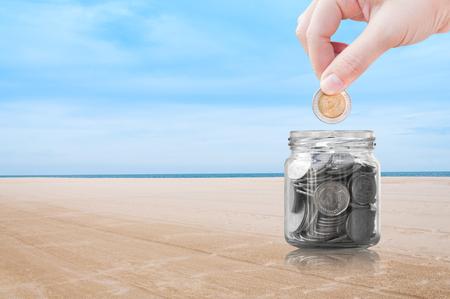 Frauenhand, die eine Münze auf Strandnaturhintergrund, Einsparung, Geldkonzept sparend, Hand setzen Geldmünze auf Glasgefäß setzt Standard-Bild - 82313696