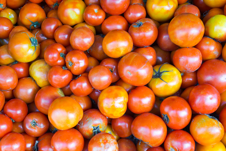 Close-up red tomatoes background. Group of tomatoes at market