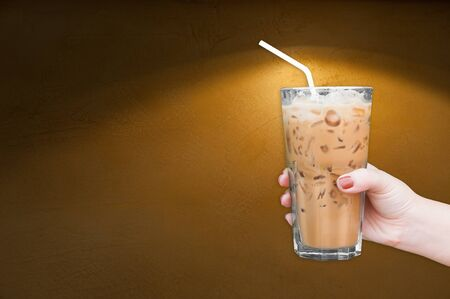 woman hand holding the glass iced coffee on brown grungy wall background