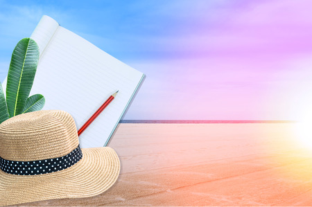 Notebook with pencil and straw hat on sea and sand of a beach nature landscape background