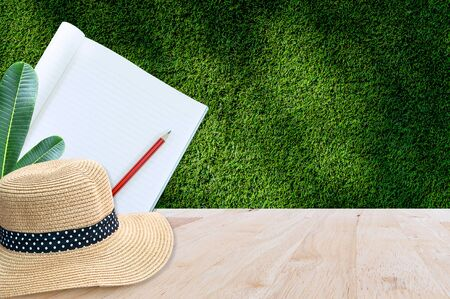 Notebook with pencil and straw hat on wooden table with green grass background,for art education background