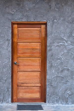 Wooden door at concrete wall texture Imagens