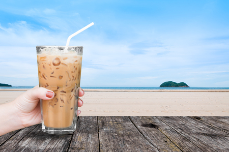 Hand woman holding the glass iced coffee on table wooden with beach landscape view nature background,Iced latte coffee