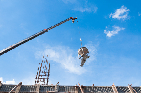 Cement or concrete bucket hanging on wire at construction site with blue sky background Banque d'images
