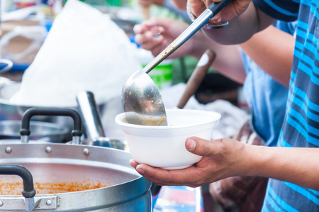 hand  holding Spoon food in the foam tray ,streetfood