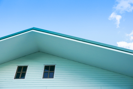 Symmetric detail shot of green roof gable showing ventilation panel with blue sky