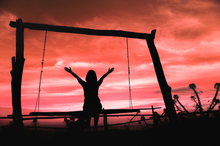 Silhouette of a woman having fun sitting on swing at sundown with beautiful clouds in background,Freedom and happiness for travel concept