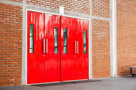 Red modern door with long stainless handle on brick wall at modern building