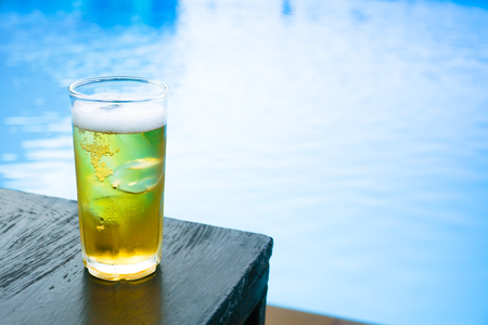 Glass of the light beer on the wooden table at the pool