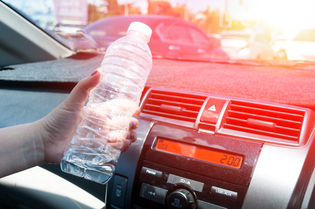 Woman hand holding a plastic bottle of water in the car