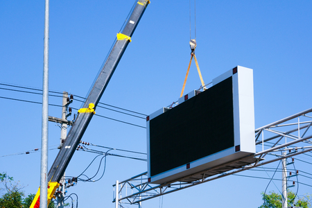 Construction site crane is lifting a led signboard Blank billboard on blue sky background for new advertisement Фото со стока