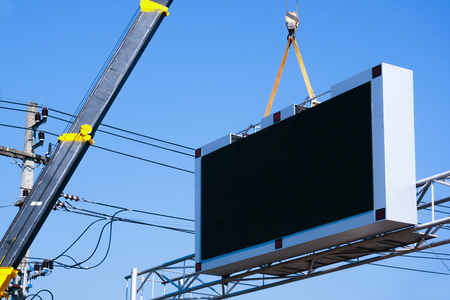 Construction site crane is lifting a led signboard Blank billboard on blue sky background for new advertisement