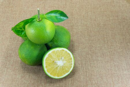 Citrus Fruit, Composition with leaves on brown fabric background