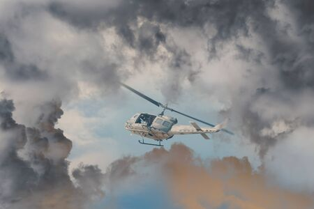 A Rescue Helicopter races against an oncoming Storm severe weather, Modern attack helicopter with with weapons Stock Photo