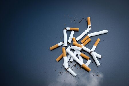 Broken cigarettes nicotine on dark background,stop smoking.Quitting from addiction concept.