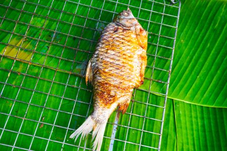 Fish burned, cooked and placed on green banana leaves,Top view
