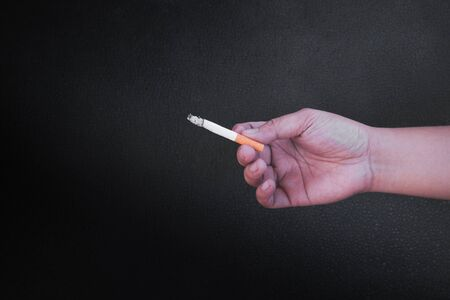 Hand is holding a cigarette on black background,No smoking. Quitting from addiction concept.