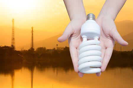 Energy saving concept, Woman hand holding light bulb on industry Landscape background,Ideas light bulb in the hand