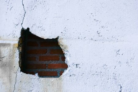 Hole in broken wall and old bricks on white background. Large crack on the wall of an old brick house, crumbling plaster and broken, cracked bricks.
