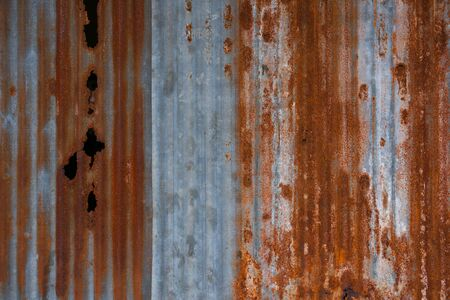 The tin roof background with the old rust and nails hole by vintage style.Galvanized iron steel plates with rust for background
